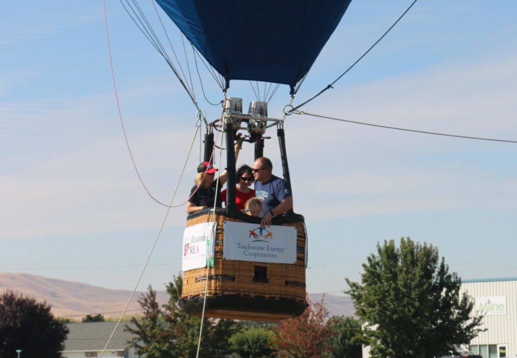A family takes a free, tethered hot air balloon ride