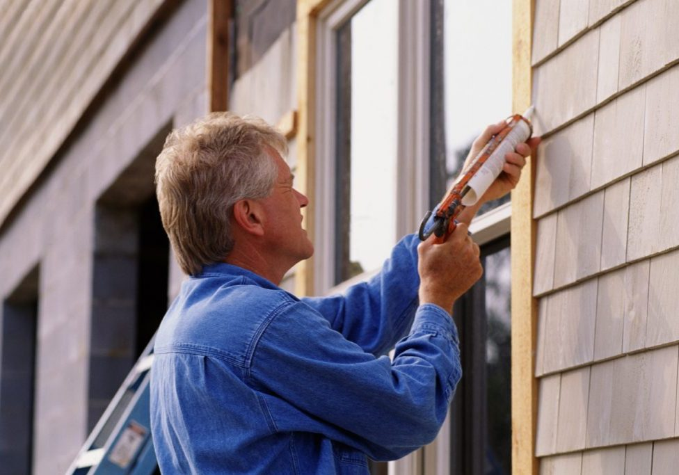 Man applying caulking to an outside window