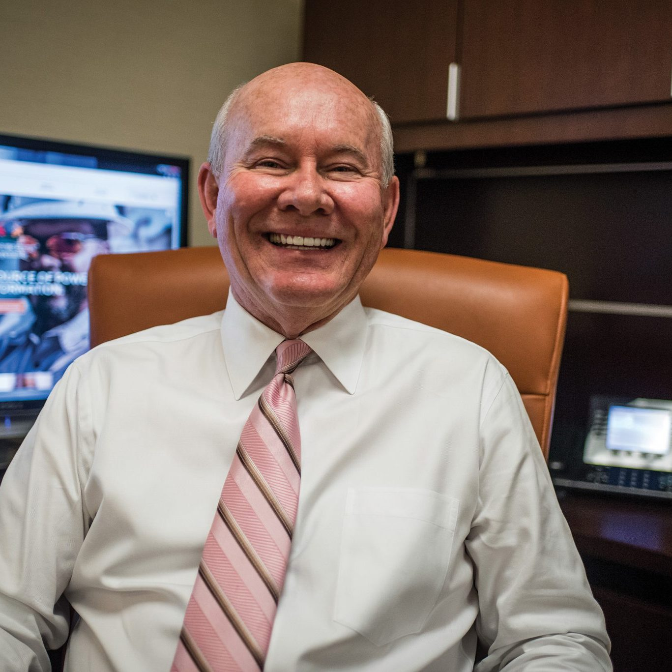 Smiling IT Professional wearing a white shirt and pink tie sitting in an office chair at his desk