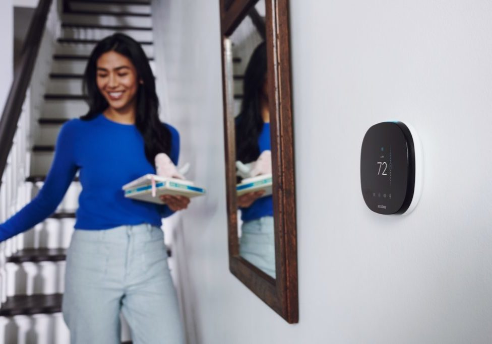 A woman walks down stairs in her home. There is a smart thermostat on the wall near her.