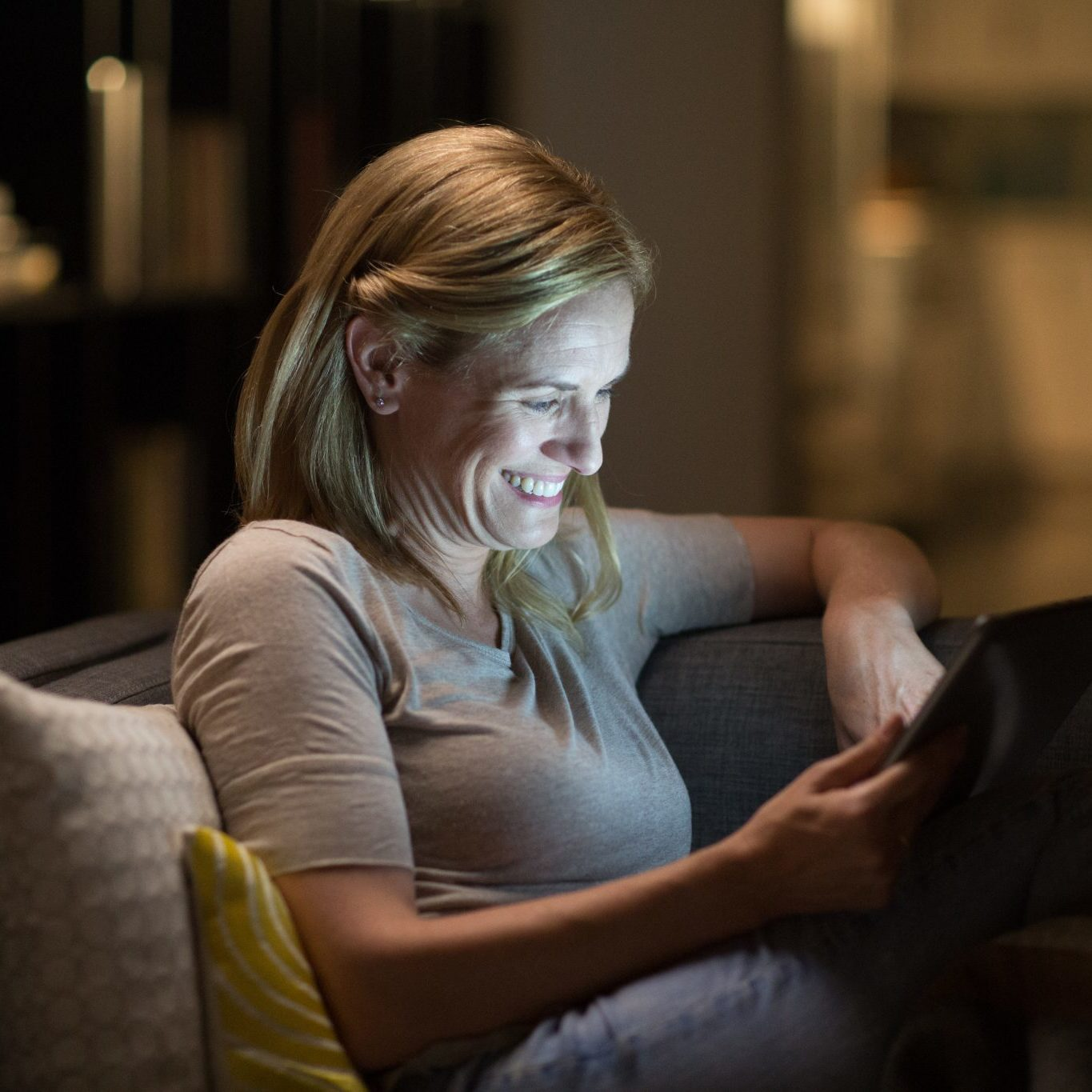 Woman sitting on couch looking at a tablet device