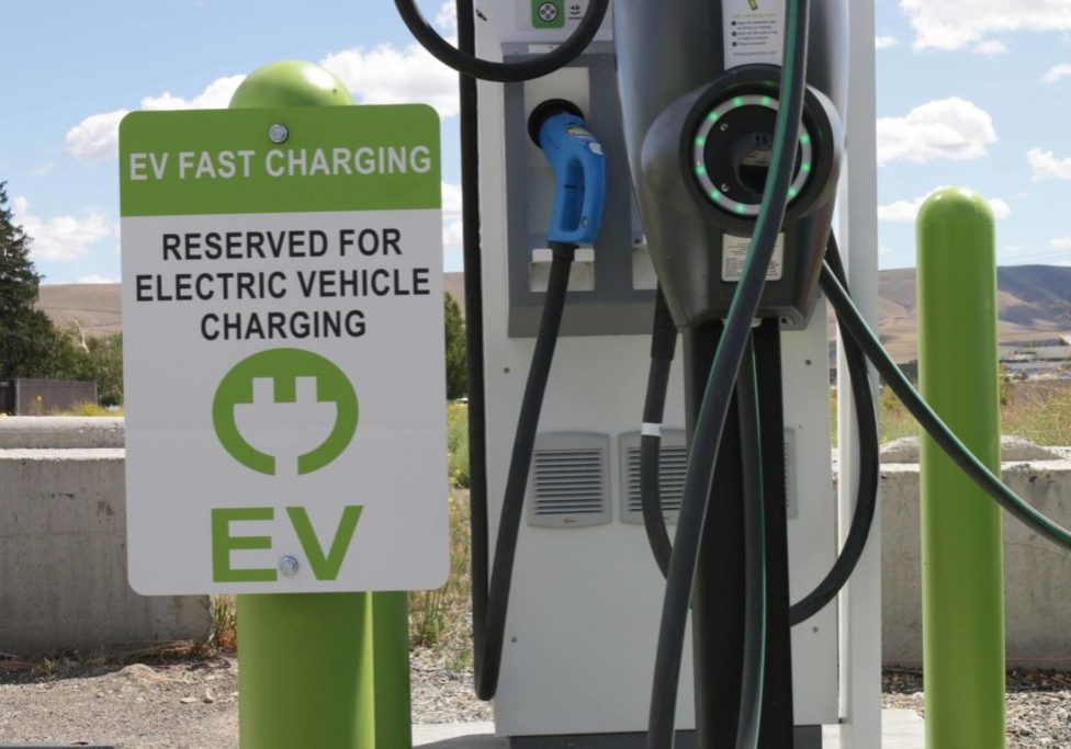 "Electric Vehicle Fast Charting station with sign that says ""Reserved for Electric Vehicle Charging"""