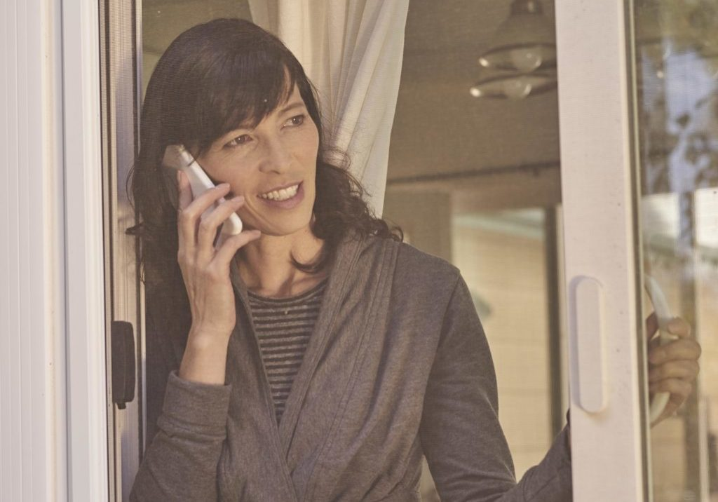 A woman stands in her sliding glass doorway with her cell phone to her ear. Scam artists use phone numbers you recognize. Do not trust your caller ID. Never give away your financial information over the phone.