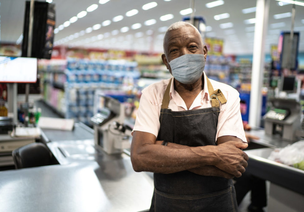 a man wears an employee apron and a mask as he stands with arms folded in a grocery or hardware store