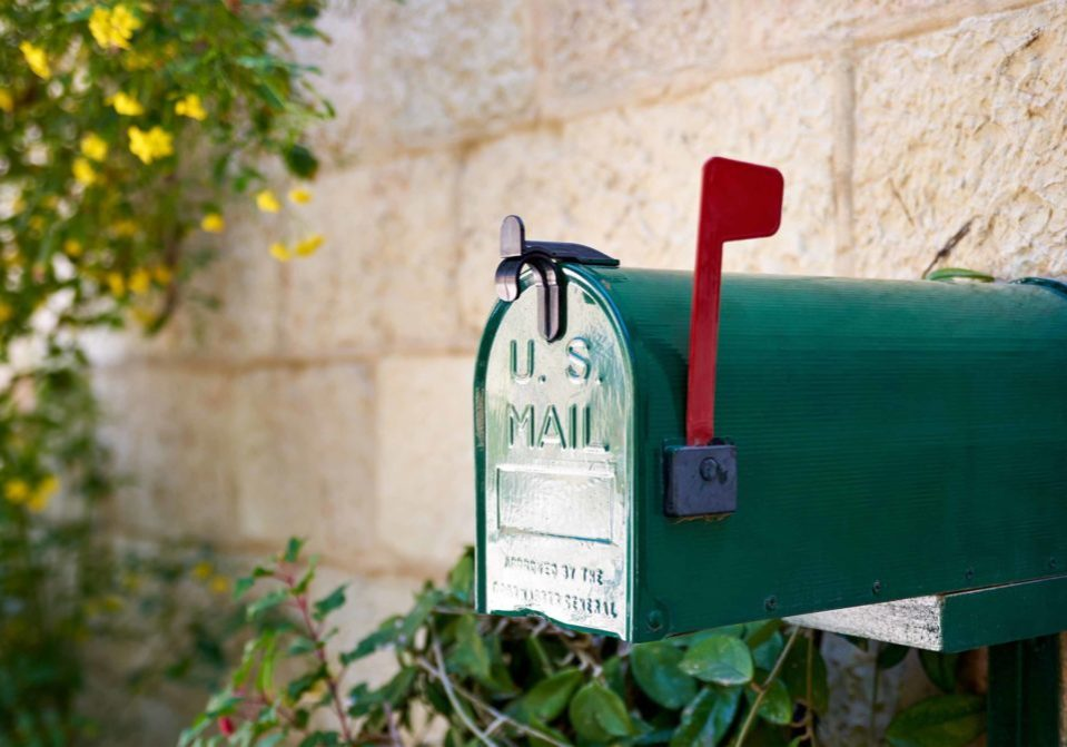 a green mailbox with a red flag up